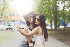 Girls friends taking selfie photos with smartphone outdoors Royalty Free Stock Photography