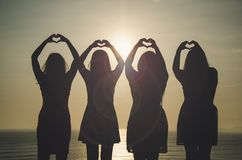 Girls in front of the sunset royalty free stock photography