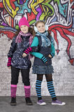 Girls in front of the wall covered with graffiti Royalty Free Stock Images