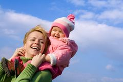 Girls fun outdoors. Woman and baby girl having fun outdoors in spring time royalty free stock photo