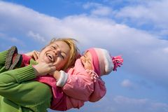 Girls fun outdoors. Mother and baby girl having fun outdoors in sunny springtime royalty free stock photos