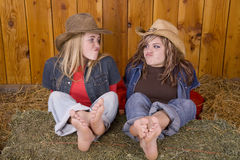 Girls funny face feet on hay Stock Image
