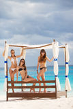 Girls in the gazebo on the background of the ocean. Three beautiful girls with a good figure,two girls in black, one girl in a white bikini, sunglasses,hand royalty free stock photo