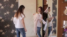Two girls measure clothes in front of a mirror. Girls get clothes from the closet and measure it in front of the mirror. Funny girls choose and measure clothes stock video