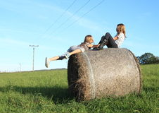 Girls getting up on package of hay Royalty Free Stock Image
