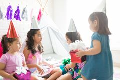 Girls With Gifts Celebrating Birthday During Slumber Party. Multiethnic girls with gifts celebrating birthday during slumber party at home royalty free stock photography