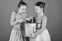 Girls with gifts. Girls with tricky faces pose with present on green background. Birthday surprise concept. Sisters with wrapped blue gift box for holiday take stock photos