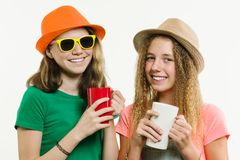 Girls girlfriends 12-14 years old, on a white background in hats talking, holding cups Royalty Free Stock Photo