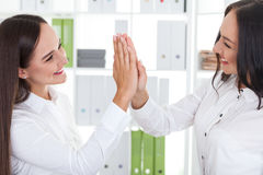 Girls giving high five Stock Images