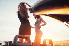Girls gladly posing next to a black car. Against the sky on a fantastic sunset Stock Images