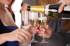 Girls and glasses with champagne wine. A man pours girls in glasses of champagne wine. Close-up stock photo