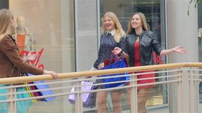 Girls go along and shop talk at the same time. Shopping, Blonde girl all dressed in beautiful dresses. Slow motion stock footage