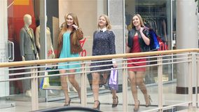 Girls go along and shop talk at the same time. Shopping, Blonde girl all dressed in beautiful dresses. Slow motion stock video footage