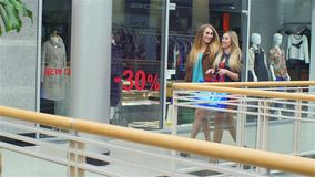 Girls go along and shop talk at the same time. Shopping, Blonde girl all dressed in beautiful dresses, Slow motion stock footage