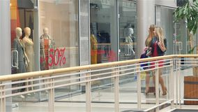 The girls go to the mall. See discounts, very. Two happy elegant women looking in shop window. The girls go to the mall. See discounts, very happy. Slow motion stock video footage