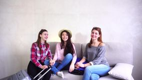 Girls going on trip preparing suitcases on couch in afternoon room. Female friends together collect large suitcases, add up all necessary things for class stock footage