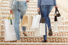 Girls going upstairs with shopping bags in hands Royalty Free Stock Photography