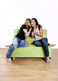 Girls gossip. Two teenage girls sharing a shocking secret or gossip while sitting on couch Stock Photo