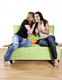 Girls gossip. Two teenage girls sharing a secret or gossip while sitting on couch Royalty Free Stock Photo