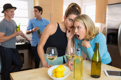 Girls gossiping about boys at a party spreading rumors and secrets Royalty Free Stock Photography