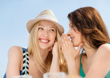 Girls gossiping in cafe on the beach Stock Image
