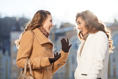 Girls gossiping. Two beautiful young women gossiping while stand Stock Photos