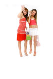 Girls Gotta Go. Two young women friends holding purses waving goodbye Royalty Free Stock Photo