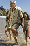 Girls And Grandfather Running Through Waves Stock Image