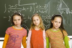 Girls at greenboard. Group of girls (5, 11 and 13yo) are standing and looking at camera. Behind them there's greenboard with maths royalty free stock photo