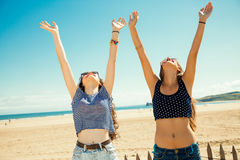 Girls greeting the sun. Funny girl friends with arms outstretched greeting the sun on the beach Stock Photo