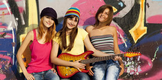 Girls with guitar and graffiti wall Stock Photo