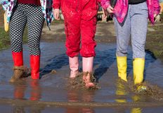 Girls in gumboots walking in puddle. Three young girls in colorful gumboots walking in puddle. Shoes for extreme rainy weather conditions Stock Photos