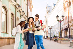 Girls and guy holding camera look at city map. Girls and guy with camera look at city map as tourists on the European street during summer day time Stock Images