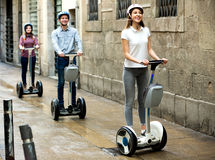 Girls and guy traveling through city by segways Stock Photo