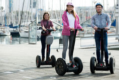 Girls and guy traveling through city by segways Stock Image