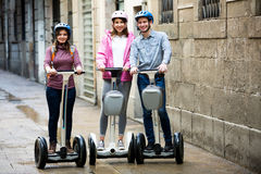 Girls and guy traveling through city by segways Stock Photos