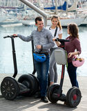 Girls and guy traveling through city by segways Stock Images