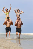 Girls and guys at the beach Royalty Free Stock Photos