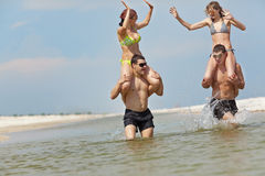 Girls and guys at the beach Stock Photos