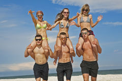 Girls and guys at the beach Stock Images