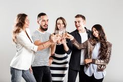 Girls and guys dressed in stylish casual clothes stand together and clink glasses with champagne. Party time royalty free stock image