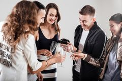 Girls and guys dressed in stylish casual clothes stand together and smile. Guy is pouring champagne in glasses. Party royalty free stock image