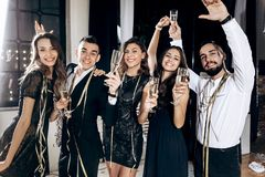 Girls and guys dressed in stylish elegant clothes having fun and clink glasses with champagne in the studio. Party time stock images