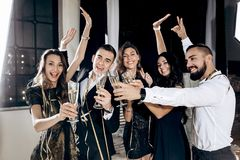 Girls and guys dressed in stylish elegant clothes stand together and clink glasses with champagne in the studio. Party royalty free stock photos