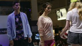 Girls and guys models show modern summer clothes on podium