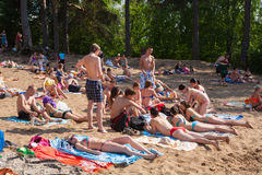 Girls and guys sunbathing in beach Royalty Free Stock Photos