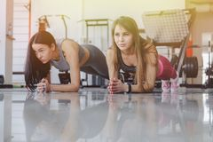 Girls in the gym stand in plank. Fitness life stock photo