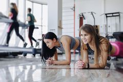 Girls in the gym stand in plank. Fitness life stock photos