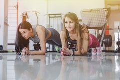 Girls in the gym stand in plank. Fitness life stock image