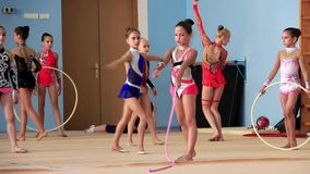 Girls gymnasts having training in gym before examination in Deriugina school stock video